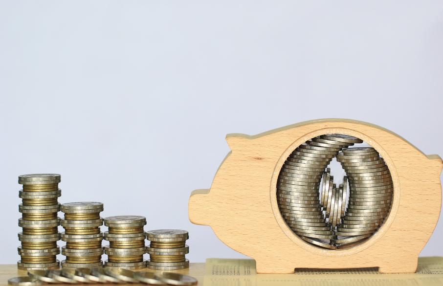 Växande mynthögar och en spargris fylld med pengar.